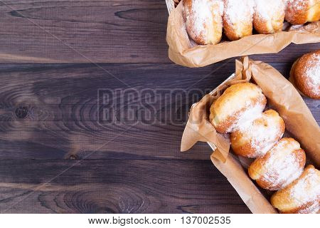 German donuts - berliner with jam and icing sugar in a box on a dark wooden background. Top view with copy space