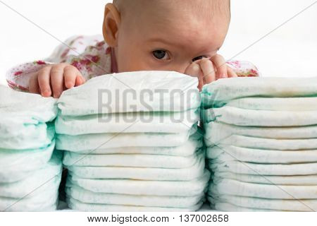 Adorable half-year baby girl hidden behind a stack of diapers.