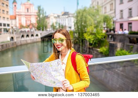 Young female traveler in yellow sweater and sunglasses standing with map on the bridge in the center of Ljubljana city in Slovenia. Traveling Slovenia