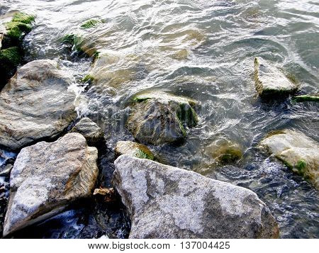 Transparent pure water washing the stones on the river bank