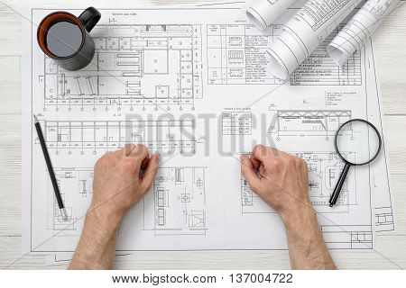 Close-up hands of architect working with a drawing. Workplace. Engineering work. Construction and architecture. Non-stop work.