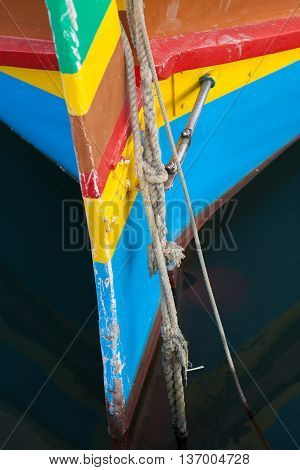 Colorful traditional Maltese fishing boat (Luzzu) moored in harbor, beautiful blue mediterranean water