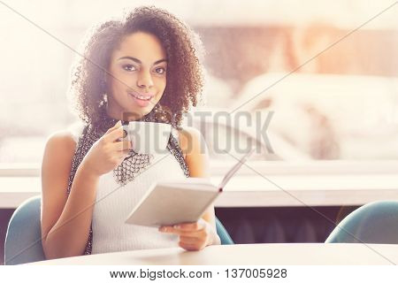 Candid one. Smiling and merry young woman holding a book and drinking coffee while sitting in a cafe and smiling at a camera