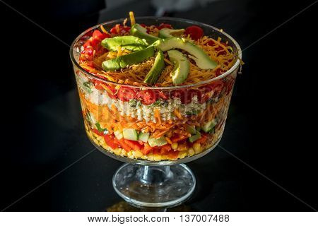 Multi Layered Salad in a Glass Trifle Bowl on black background