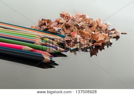 Sharpened colorful pencils and pile of colorful pencil shavings on black glass gloss table with medium depth of focus