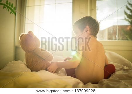 A little cute boy with Teddy bear on the bed (Note: Lens flare with harsh light and desired retro effect)