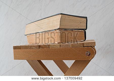 Vintage old books on wooden stool. white blackgrownd