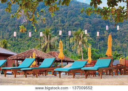 asian tropical beach with sunbeds under trees