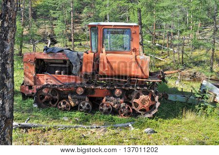 An old tractor lost and asleep in the forest in Eastern Yakutia on the shore of the nameless lake.