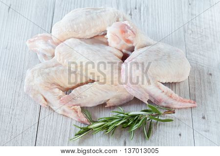 Raw chicken wings with rosemary ready to be cooked.