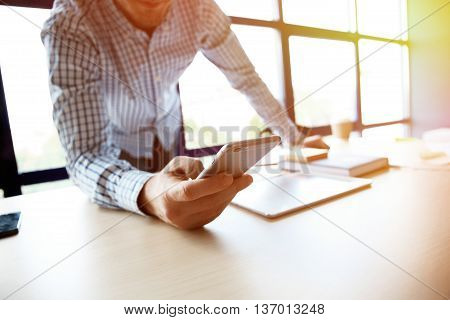 Young businessman working with modern devices, digital tablet computer and mobile phone. Analyze plans, papers, hands keyboard. Blurred background, film effect
