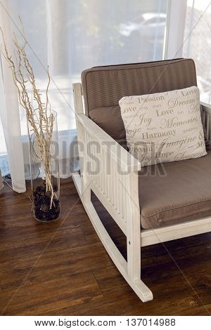 white rocking chair with brown cushion in the interior against white curtains