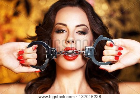 Sexy woman bite handcuffs red lips bdsm