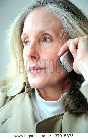 Mature female blond beauty talking to client on her cellphone.