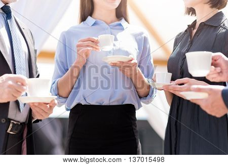 Have a rest. Pleasant colleague holding cups and drinking coffee while having a pleasant conversation