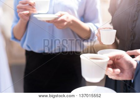 Pleasant time spending. Close up of cup of coffee in hand of a nice man holding it while drinking coffee with his colleague
