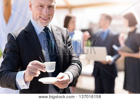 Join me. Positive delighted smiling handsome man holding cup of coffee and going to drink it while his colleagues talking in the background