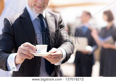 That is for you. Close up of cup of coffee in hands of pleasant handsome cheerful man holding it while his colleagues working in the background