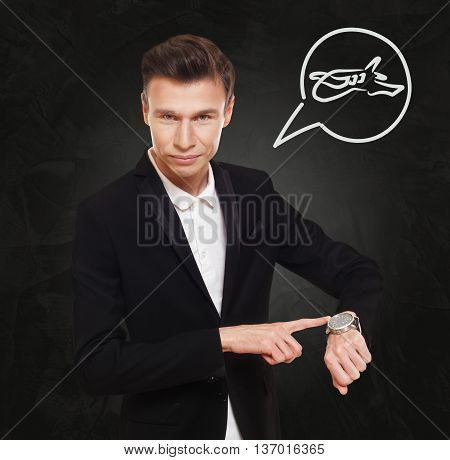 Time to fly. Businessman point at his watch showing time is money concept. Man in suit with clock at black background, thinking cloud with plane sign. Flight departure, late at business trip.