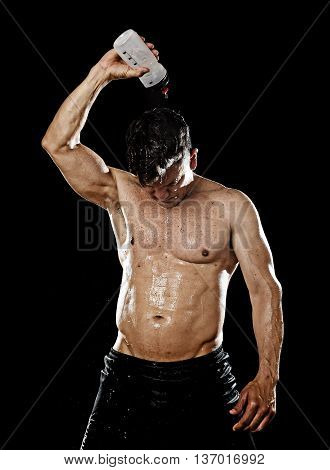 attractive strong sport man pouring water on his head sweating tired after training hard on gym bodybuilding workout isolated on black background in health care hydration and fitness concept