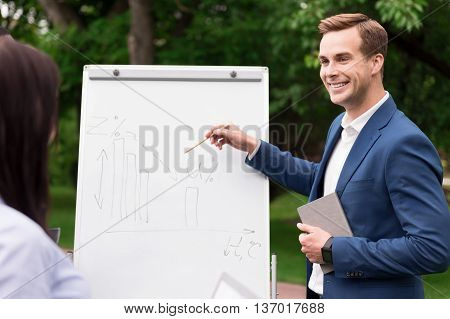 Involved in work. Positive handsome smiling man standing near board and pointing it while working on the project with his colleague
