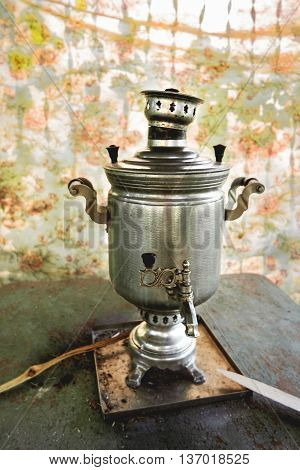Brass samovar tin-plated. Vintage Russian device to heat water by firewood for beverages. Old fashioned antique metal kettle. Rustic background.