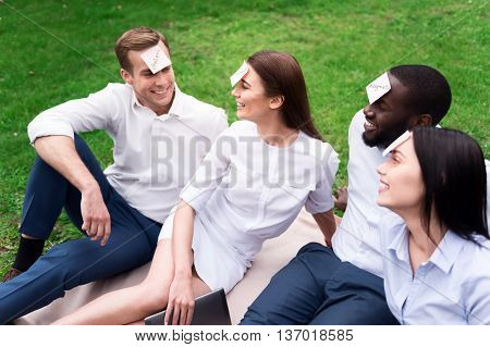 Involved in fun. Positive content smiling friends sitting on the blanket and having fun while resting together