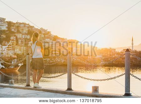 Young blond woman watching sunset in sea port of Alanya, Turkey, Mediterranean region.