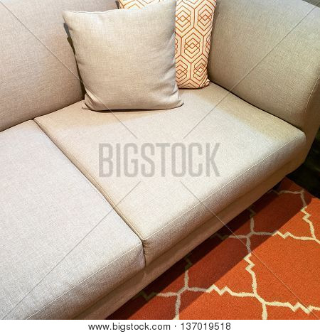 Comfortable gray sofa with cushions on orange carpet.