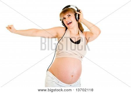 Happy pregnant woman listening music in headphones isolated on white