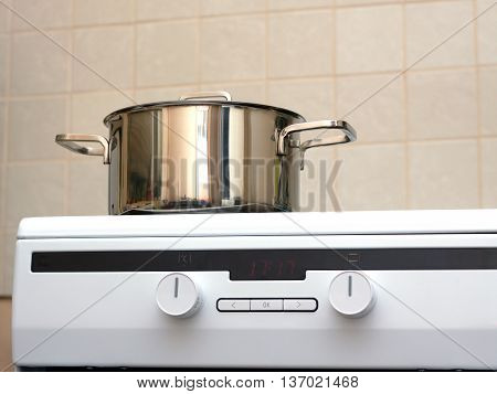 Metal steel saucepan with lid on modern kitchen electric stove. Photo closeup