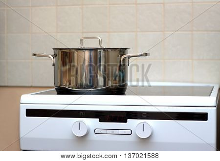 Metal steel saucepan with lid on modern kitchen electric stove. Front view closeup