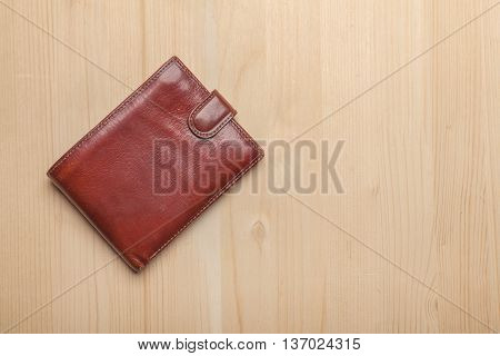 brown leather wallet on wooden table with copy space at right side