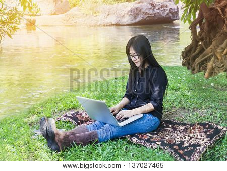 Blank Screen Laptop With Girl Sitting On Grass Field At Riverside