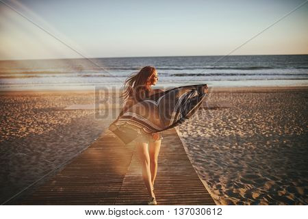 Back view of unrecognizable girl walking on wooden path on beach with analog film efect