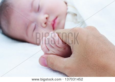 Close up hand of parent clasping hand of sleeping child. Shallow depth of field (DOF). Hand in focus Asian child out of focus.