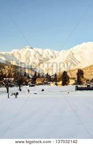 Alpine landscape of snow covered village and mountains on Honshu, Japan.