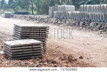Cement sheet stack near the cement pipe stack in the construction site.