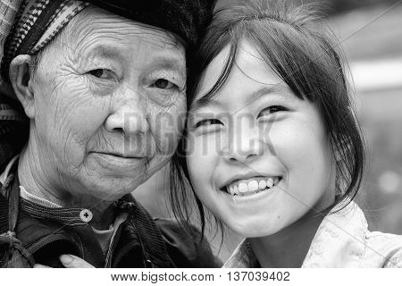 Ha Giang, Vietnam - September 21st, 2015: Smile ethnic granddaughter headrest beside beloved grandmother expressed reverence, joy optimism in lives minority people in Ha Giang, Vietnam