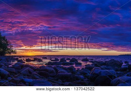 Panorama of stony coast of Baltic sea by vivid sunset with fiery cloudscape