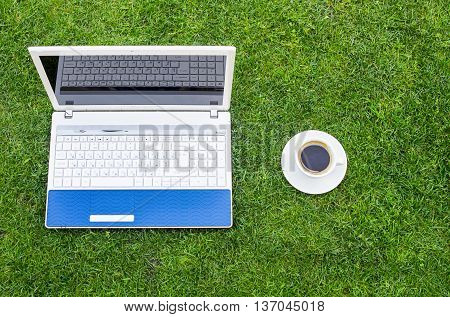White Laptop coffe cup and pen Placed On Green Grass Field.
