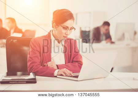 Female business executive working on laptop in office