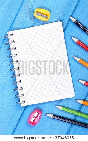 Colorful Crayons, Sharpener And Notepad On Blue Boards, School Accessories, Copy Space For Text