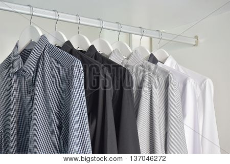 row of white gray black shirts hanging in wooden wardrobe