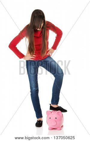 Young woman with piggybank under leg.
