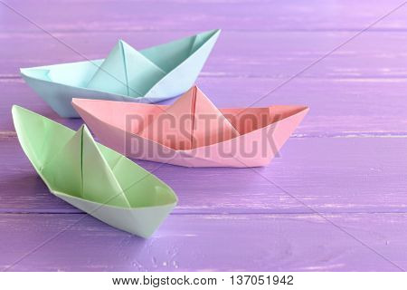 Pink, green, blue paper boats on lilac wooden background. Paper folding techniques. Easy origami crafts for kids to do. Origami toys boats for children