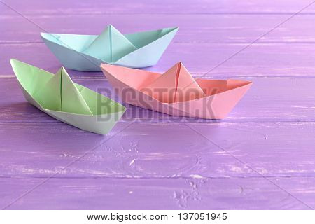 Three colorful paper ships on lilac wooden table. Easy to make origami boats. DIY origami boats for children. Summer paper crafts idea for kids