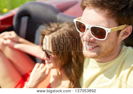 leisure, road trip, travel, summer holidays and people concept - happy couple driving in cabriolet car and hugging