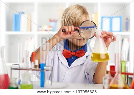 Curious boy looking though magnifying glass at the liquid in beaker