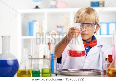 Portrait of schoolboy amazed with chemical reaction